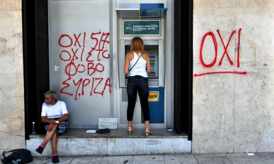 """A woman withdraws money from an ATM machine in Thessaloniki, Greece next to a beggar and graffiti reading """"no to fear""""."""