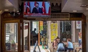 Turkish finance minister, Berat Albayrak, speaks on TV while people drink tea in Istanbul