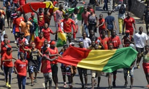 Protesters take to the street in Conakry while carrying the Guinean national flag.