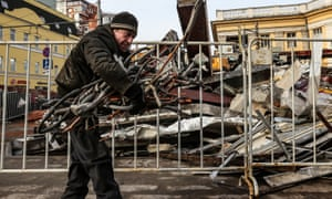 A man collects scrap wires near demolished shops at the entrance to Novoslobodskaya metro station