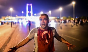 A man covered with blood stands near the Bosphorus Bridge as the Turkish military clashes with civilians at the entrance to the bridge in Istanbul.
