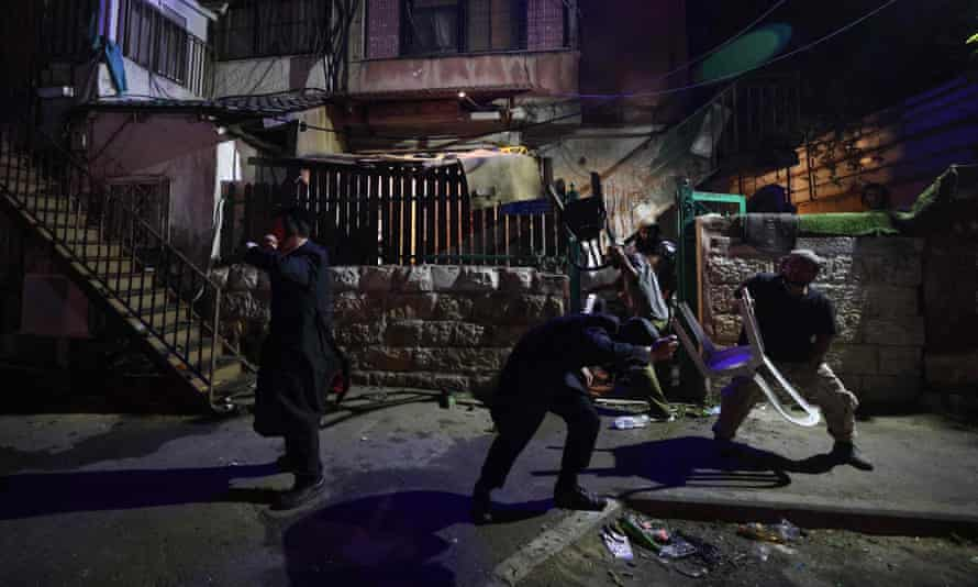 Israeli settlers take cover as projectiles are thrown at them in the Sheikh Jarrah neighbourhood of occupied east Jerusalem, on May 5.