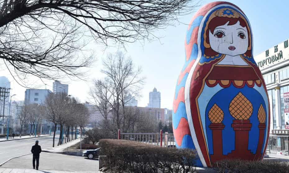A man walks past a giant statue of a Russian Matryoshka doll on a street in Suifenhe
