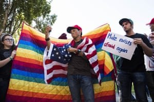 A protester takes a selfie while counter-protesters hold a rainbow blanket behind him, during demonstrations responding to the cancelled No Marxism rally, Berkeley, California, US