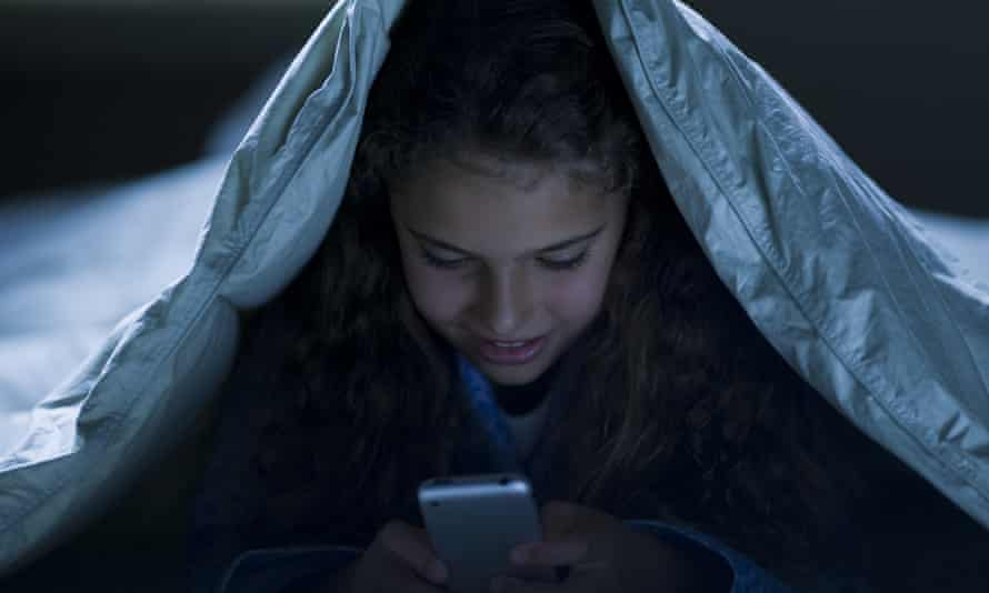 Girl under blankets at night with a smartphone