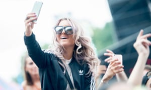 A reveller holds her phone at Lovebox Festival in Victoria Park, London, on 15 July 2016