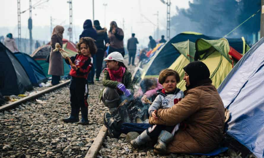 A woman sits with a child on her lap by railway tracks at a makeshift camp near the Greek village of Idomeni.