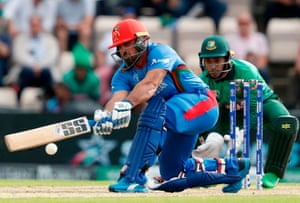 Afghanistan's Najibullah Zadran is watched by Bangladesh's wicketkeeper Mushfiqur Rahim as he plays a shot.