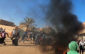 Demonstrators flee as teargas is fired by riot police during an anti-government protest in Omdurman in January