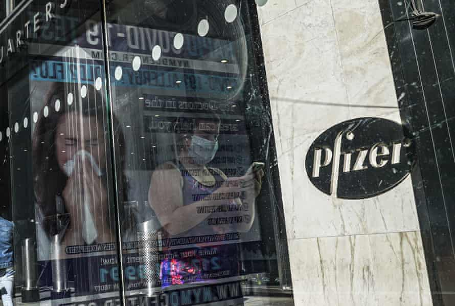 In this Nov. 9, 2020, file photo, an ad for COVID-19 testing reflects on glass at a bus stop, as pedestrians walk past Pfizer world headquarters in New York. Pfizer and BioNTech say they've won permission Wednesday, Dec. 2, 2020, for emergency use of their COVID-19 vaccine in Britain, the world's first coronavirus shot that's backed by rigorous science -- and a major step toward eventually ending the pandemic.