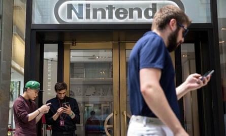 Two men play Pokémon Go outside Nintendo's flagship store in New York.