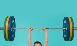 The top of a young boy's head and his arms holding a bar with heavy weights on