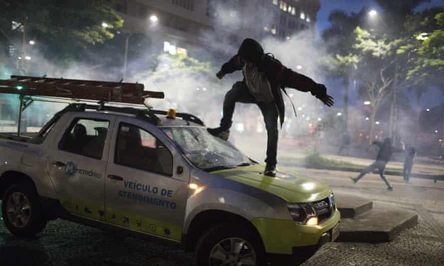 A demonstrator breaks the windshield of a truck in Rio de Janeiro.