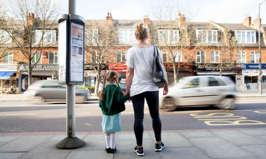 A child and woman wait at a bus stop