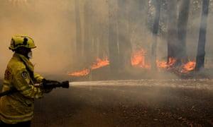 A Gloucester fire crew member fights flames at Koorainghat, near Taree