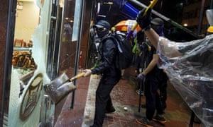 Demonstrators smash a mahjong shop run by mainland Chinese during a protest in Hong Kong.