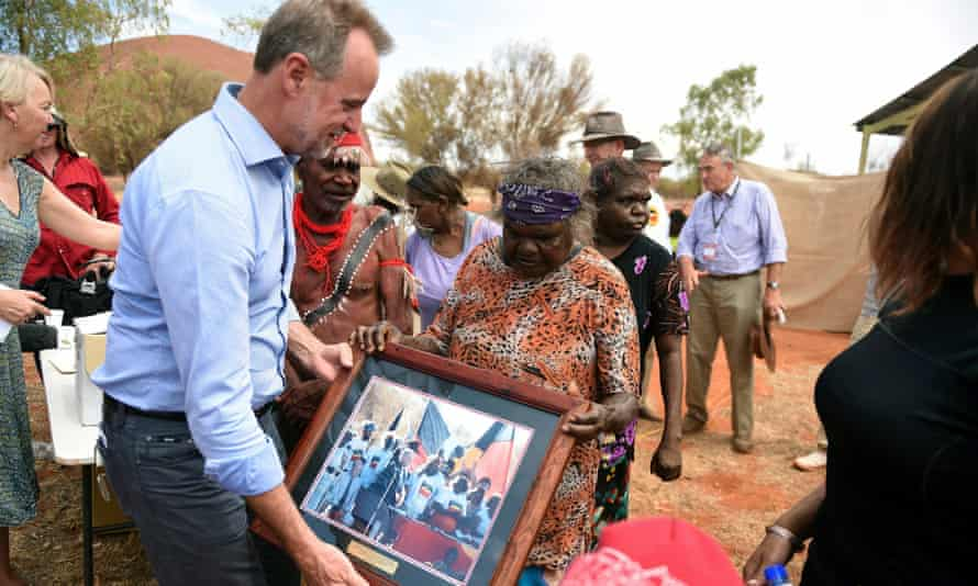 Minister for Indigenous affairs, Nigel Scullion presents a photograph from the original handover of Uluru to families who were there in 1985.