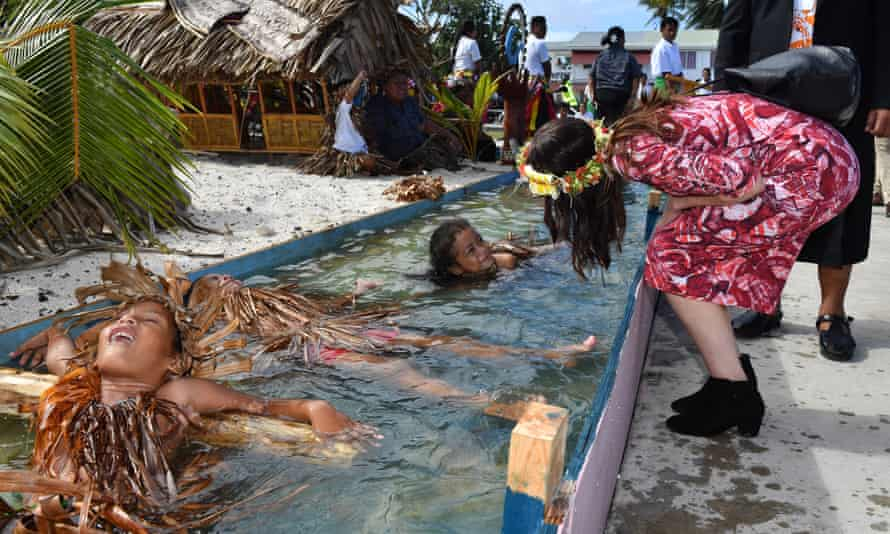 Children symbolically representing climate change greet New Zealand's PM, Jacinda Ardern, as she arrives for the Pacific Islands Forum.