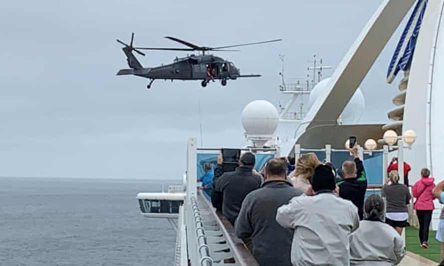 Passengers on board the Grand Princess watch while a US military helicopter delivers coronavirus tests.