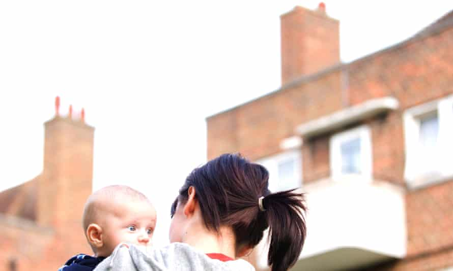 Woman holding baby on council estate.