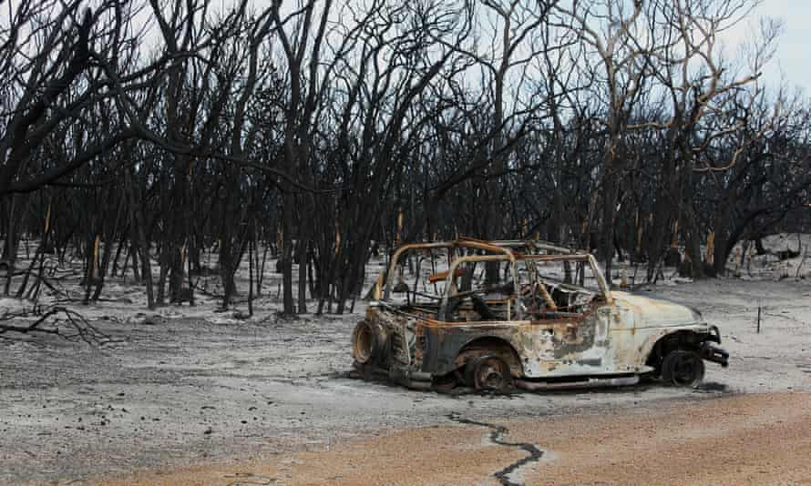 a burned out car next to a burned out wood in australia