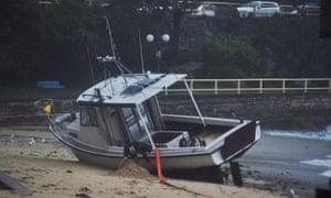 epa04714093 A man attempts to dig his boat off the beach at Manly Cove in Sydney, Australia, 21 April 2015. More than 20 people have been rescued from floodwaters and 215,000 homes and businesses are without power as storms continue to lash South Eastern Australia.