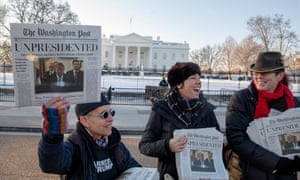 Volunteers distribute fake editions of the Washington Post, dated May 1, which predict Trump leaving office after months of women-led protests.