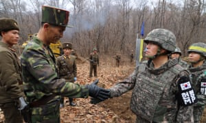 North and South Korean soldiers shake hands during an operation to reconnect a road across the military demarcation line inside the demilitarised zone.