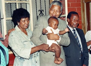 Winnie and Nelson Mandela play with their grandchild Bambata at their Soweto home in 1990