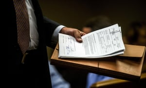 Special agent Jeff Seipenko walks out of the courtroom with signed paperwork authorizing charges Wednesday in Flint, Michigan.