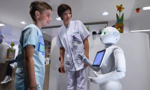 A young boy talks with the robot Pepper next to a nurse during a press conference at the CHR Citadel hospital centers of Liege.