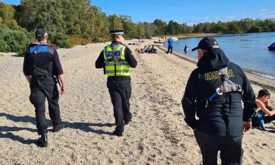 Rangers and Police Scotland officers on patrol on Inchmoan South Beach, Loch Lomond and the Trossachs national park.