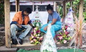 Fa'aoso Tuivale and her husband, Tuivale Luamanuvae Puelua sit on their children's graves in Lauli'i, Samoa.