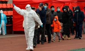 A worker wearing a protective suit leads residents to a makeshift Covid-19 coronavirus testing centre in Tianjin on 21 November after new coronavirus cases were detected in the city.