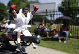 A Muhammad Ali action figure sits on the seat of a bicycle as fans wait for the funeral procession