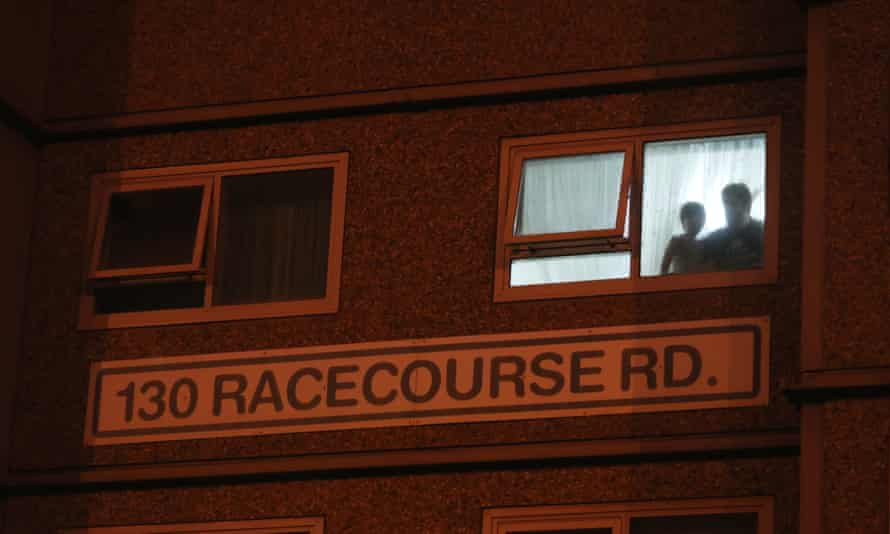 Residents watch from their window as police enforce a 'hard lockdown' at public housing towers in Flemington, Melbourne.