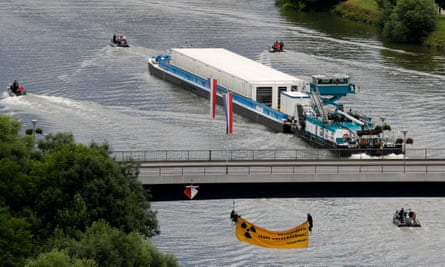 A ship carries nuclear waste containers along the Neckar in Bad Wimpfen, Germany, as environmentalists hang under a bridge to try to block it.