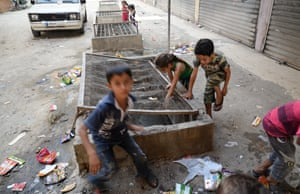 Children play in the street outside the factory