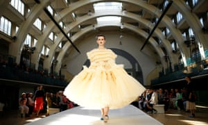 Model in wide yellow dress on catwalk in striking arched building