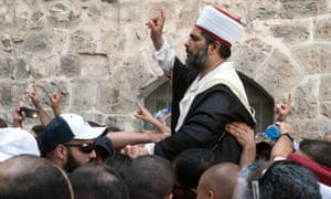 An official of the Waqf, the Islamic institution that administers the compound housing the al-Aqsa mosque, is carried shoulder high by Palestinian worshippers to one of the main entrances to the shrine.