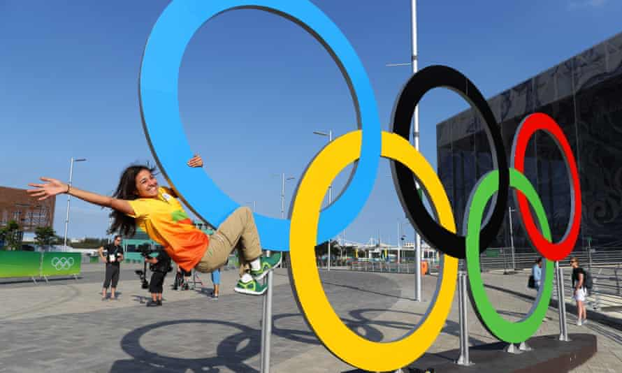 A Games volunteer and fan of the Olympic Rings in the Barra Olympic park.