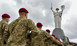 Soldiers march by the 102-metre-high Motherland monument in Ukraine.