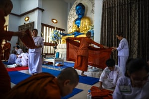 Devotees and monks fold their saffron robes during a practice session ahead of their ordination to be novice monks