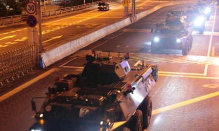 Chinese military vehicles move across the border into Hong Kong on Thursday.