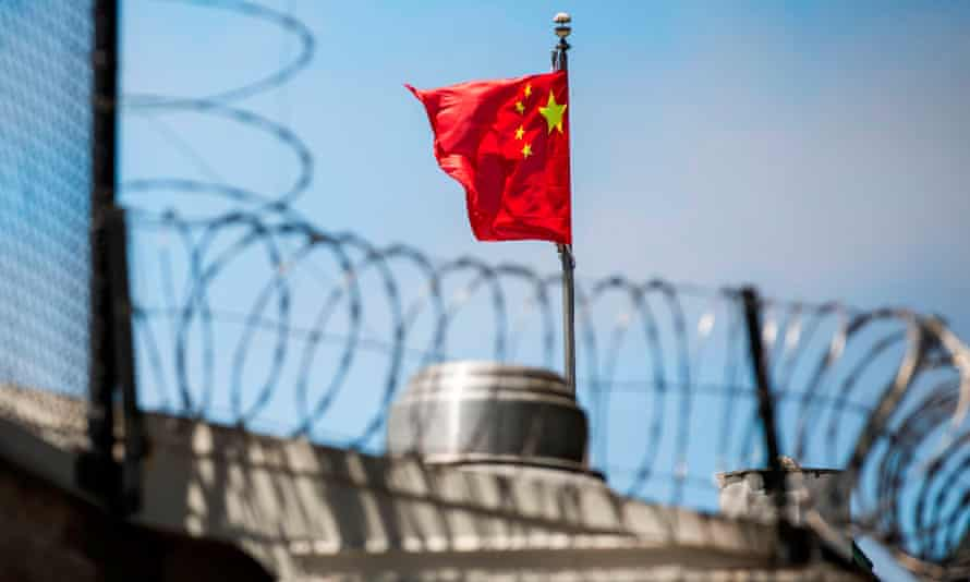 Chinese flag flies behind barbed wire at the Chinese Consulate General in San Francisco