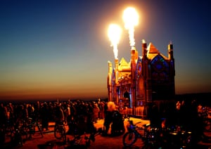 Hundreds of Burning Man attendees dance in the pre-dawn darkness in front of mobile music platform that's blasting both techno and fire