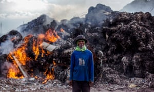 Indonesian scavanger Suparno, 60, stands in front of burning plastic waste at an imported plastic dumpsite in Mojokerto