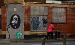 A woman walks past graffiti in Gipsyville
