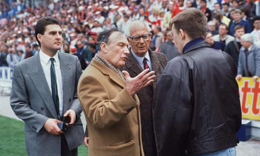Graham Mackrell, left, looks on as the Liverpool chairman, John Smith, talks to a fan at Hillsborough.