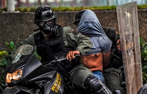 Riot police arrest an opposition activist during clashes following mass protests  against president Nicolas Maduro.